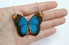 Each butterfly pendant is made by applying vintage butterfly illustrations to wood, and then laser cutting. Finally it is sealed for protection, and attached to a silver chain, making a pretty necklace. The butterfly me. Mandala Jewelry, Butterfly Jewelry, Butterfly Pendant, Butterfly Necklace, Monarch Butterfly, Blue Butterfly, Wooden Necklace, Wooden Jewelry, Resin Jewelry