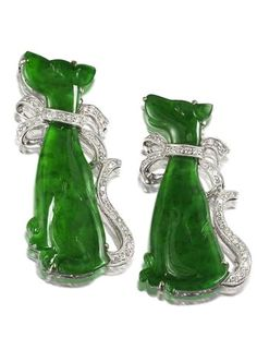 A pair of jadeite and diamond brooches The intense green jadeites of good translucency, the two largest pieces measuring approximately 32.0 x 16.2 x 2.5mm and 28.6 x 18.4 x 2.4mm, carved as two dogs, to a tail and stylised ribbons set with brilliant-cut diamonds, mounted in 18k white gold.