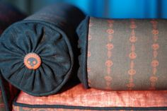 """Skull Button Ghost Paisley Bolsters $30.00 Playful ghosts wrap around this cylindrical bolster with black linen welt and black linen end caps.  Matching skull buttons add the perfect finishing touch.  It has a zipper closure and includes insert.  Color(s): Red and Black Design(s): Ghost stripes  Material(s): 100% polyester Eco Canvas made from 45% recycled material, linen, $ cotton. Measurements: 15"""" long x 5"""" diameter Miscellaneous Information: Matching bench available here."""