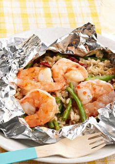 Paquetitos de camarones con arroz- Una mezcla de ejotes (habichuelas verdes), arroz y tomates secados al sol se lía con los camarones en paquetitos de papel aluminio en la parrilla para un sabroso platillo que también es fácil de limpiar.