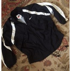 Vintage Nike Windbreaker Coat very cool black and white Nike windbreaker jacket/coat. this is pretty lightweight for a coat but has a mesh lining that would be perfect for a milder day. black with white accents and Nike swoosh on chest. has a waist cincher but the elastic is very old. the zipper pull is missing but the zipper works. you just have to push/pull it with your hand Nike Jackets & Coats