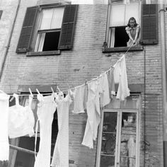 A woman hanging out the laundry. Photograph by Alfred Eisenstaedt. New York City, 1939.