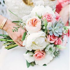 White peonies, peach garden roses, succulents, white lisianthus and seeded eucalyptus combined for a bright floral bouquet fit for an elegan...