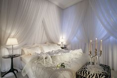 Romantic Canopy Bed Ideas with White Wall Paint Color and Awesome White Curtains Canopy and Double Black Circle Table Lamps also Unique Ottoman Design and White Cushions