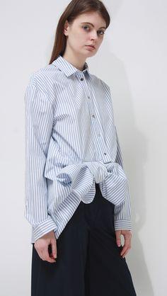 Asymmetric, bow-embellished hem in striped shirt. Light blue and white poplin.