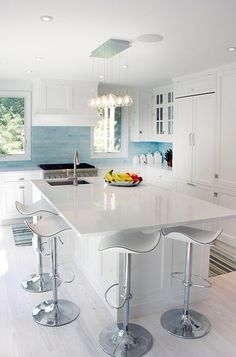 Elsa Soyars    white  turquoise blue contemporary kitchen design with white modern kitchen with white cabinets, blue glass tiles backsplash, striped blue green brown rug, kitchen island, marble countertops, modern counterstools and pendant lighting.