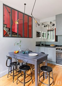 I like this monochrome kitchen with industrial elements. The red window just adds an interesting point to the picture. Designer MARIANNE EVENNOU.