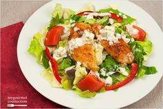 A crisp, green dinner salad topped with crispy chicken tenderloins bathed in sweet Thai chili sauce and butter and a creamy, buttermilk ranch dressing and chunks of blue cheese.