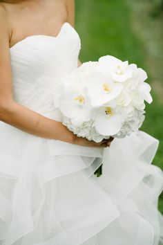 All white rose and orchid wedding bouquet: http://www.stylemepretty.com/new-york-weddings/long-island/the-hamptons/sagaponack/2017/03/17/gorgeous-hamptons-dinner-party-or-wedding-you-decide/ Photography: Brian Hatton - http://brianhattonweddings.com/