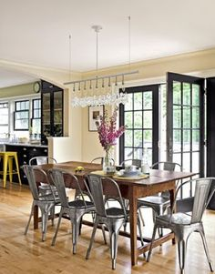 An eclectic dining room with a wood dining table, metal schoolhouse-y chairs and a linear crystal chandelier