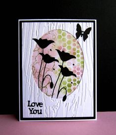 """By catluvr2 at Splitcoaststampers. Focal image background: Sponge through stencils (Distress inks peeled paint and victorian velvet). Add piece to black cardstock panel. Dry emboss white panel (wood folder); die cut oval from piece. Attach white panel to black panel. Tuck die-cut flowers (""""Prim Poppy"""" by Memory Box) so bottoms of stems are behind white panel but one bloom is on top of white panel. Add sentiment, butterfly, and white card base."""