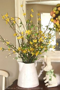 Pretty pop of yellow forsythia in a crisp white vase. Charming ceramic white bunny. Nice for Easter and #SpringDecorations
