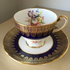 Hammersley Vintage Teacup and Saucer This teacup and saucer has a stunning gold overlay design on a dark cobalt blue. In contrast is a bright white with flower bouquets. The bouquets consist of many muted colours of pink, yellow, white, blue and purple. This set is eye catching and will stand out in any collection. Made In England Fine Bone China Back Stamp dates: 1939-82 Measurements Cup: 7cm high, 8.8cm across(not including handle) Saucer: 14.2cm across This set is in Excellent Used…