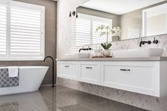 hamptons style bathroom with freestanding bath tub and marble herringbone tiles