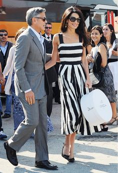 Amal Clooney steps out with her husband, George, in a casual midi contrasting striped dress and black bow pumps.
