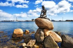 The Little Mermaid statue Copenhagen. The statue was commissioned in 1909 and unveiled in Hans Christian Andersen, the author of The Little Mermaid is a native Dane. Little Mermaid Statue, The Little Mermaid, Grand Cayman, Hans Christian, Mermaid Sculpture, Place To Shoot, Old Fort, Photography Guide, Madrid