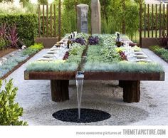 Outdoor dining table with plants and water.