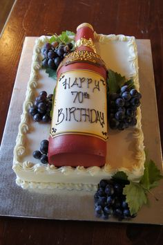 Red wine bottle birthday cake with customized label and grapes on top of sheet cake