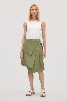 Designed with a folded waist detail, this skirt is made from dense cotton twill. A wrap-over style that sits between the hip and the waist, it has an asymmetric hemline and straps on the side.