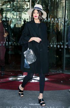 Selena Gomez wears a ruffle-sleeve coat, leggings, clutch, mules, and a straw hat