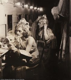 The show must go on: Chorus girls are pictured setting their hair in neat waves in rustic Hollywood mirrors.