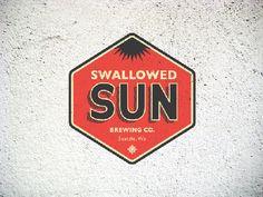 Le logo vintage moderne de Swallowed Sun en forme de blason hexagonal.