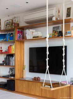 apartamento de estilo escandinavo com estantes de marcenaria e balanço no meio da sala