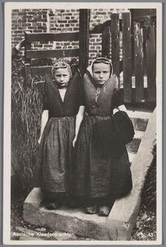 Twee meisjes in Axelse streekdracht. Het linker meisjes draagt over het oorijzer een 'capote' (type meisjesmuts), welke werd gedragen tot rond het 7e levensjaar. Het rechter meisje draagt over de ondermuts en het oorijzer een 'ronde muts' of 'hernhutter' (type muts), welke gedragen wordt tussen het 7e en 14e levens jaar. 1923-1935 #Zeeland #Axel