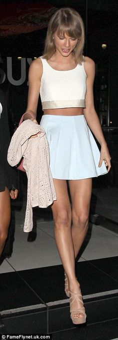 Taylor Swift wears a blue mini skirt and a white crop top to dinner with friends