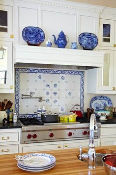 Country French Kitchen in Blue and White A white kitchen boasts blue accents and country themes. Antique Chinese Cantonware and blue-and-white transferware pop against the kitchen's neutral canvas. Intricate moldings help tie the room to the home's 1936 origin.