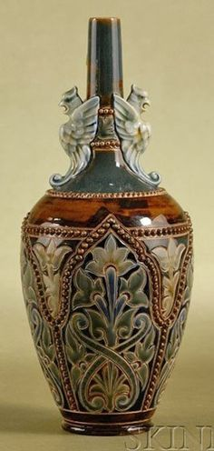 A Doulton Lambeth Vase, by Arthur Beere and Emma burrows, griffin-form handles above a tapered body with overall design of scrolling foliage in tones of green and blue on a brown ground, England, circa 1875-1885