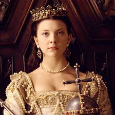 Anne Boleyn, as portrayed by Natalie Dormer, holding the orb and scepter of a Queen of England.