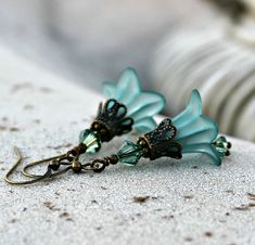 A lovely pair of teal and swarovski crystal flower earrings.  The lucite flowers are 16 mm lily flowers in a lovely frosted teal. Antique brass