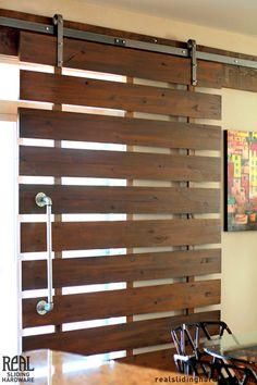 Sun control - Slatted sliding door with barn door hardware.