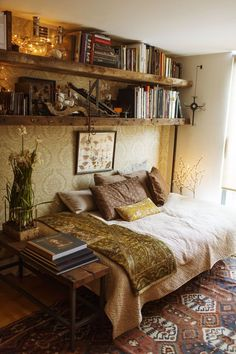 Incorporate bookshelves into a small bedroom space by hanging them near the ceiling. This room is so rustic and cozy!