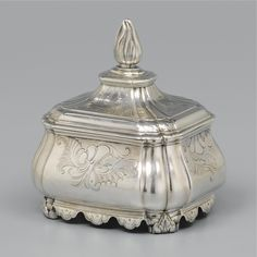A DUTCH SILVER TOBACCO JAR, JAN DIEDERIK PONT, AMSTERDAM, 1756 lobed at the angles, chased and engraved with rococo shells and leaves, detachable cover alternating lobes, cone finial, four bifurcated scroll supports, engraved initials C. B  / AG below the base, fully marked below (2) 571gr., height 14.8cm.