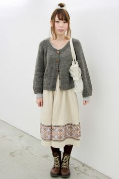 """Even mori girls have to go out in public sometimes, and that can mean toning the raggediness down. Here, the textured gray cardi (with top button that plays up an a-shaped, waist-less silhouette) and leather boots are traditional, but the lack of gauzy volume on the ivory dress–in what looks like simple sturdy cotton–keeps the look from being overly romantic. The """"ethnic"""" printed border on the dress creates visual interest on a simple look, and also is a nod to mori s..."""