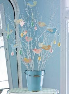 Country or vintage interiors will love this simple metal pail in baby blue, white painted branches hung with pastel coloured paper (or wood) birds and painted blown eggs. Fantastic as a hallway Easter statement piece (cover table with a gingham cloth for extra country appeal).