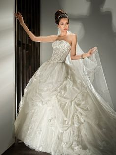 2843 Beaded, Strapless Tulle, Ball Gown with a Corset bodice and Lace-up back. Draped, Tulle Skirt features ruffles and Lace underlay. Sample shown-Ivory/Sheer