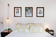 Quarto clean e relaxante com pôsteres de Rita Wainer e luminária feita pela dona da casa.