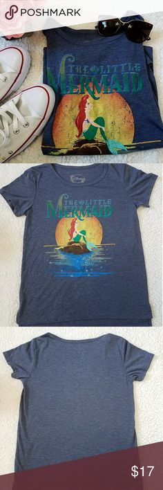 """Disney Little Mermaid t-shirt  Never worn, New Condition  This t-shirt features Ariel sitting on a rock gazing up at the sky.  """"The Little Mermaid"""" title is at the top.  Slight high/low.  Perfect for any Disney fan.  Disney Tops Tees - Short Sleeve"""