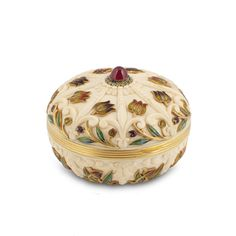 BOUCHERON. AN ENAMEL AND IVORY POWDER COMPACT. Of annular form, the lid with carved fleur-de-lys motifs, embellished by weaving tulips applied with multicolored enamel, centering on a cabochon ruby within blue enamel border, opening to reveal a feather powder-puff with a carved ivory handle, completed in December 1899, signed F. Boucheron, Paris, maker's mark for celebrated designer and jeweller Georges Le Saché.