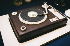 A groom's cake made to look like a real record player!  Dark chocolate cake with airbrushed fondant.  All decor is hand-sculpted gumpaste/candy and completely edible.