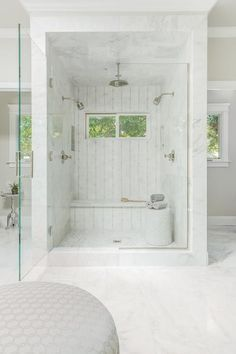 Fabulous master bathroom features a marble shower, placed in the center of the room, lined with his and hers shower heads facing each other as well as a marble shower bench under windows.