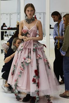 A deconstructed corset dress with trailing garden flower embroideries is fitted in the Paris atelier in the days before the Alexander McQueen Spring/Summer 2018 show. Photograph by Sir Don McCullin.
