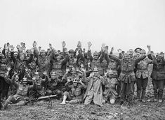 Men of the 1st Anzac Division, some wearing German helmets, pose for the camera after fighting near Pozieres Ridge. July 23, 1916.