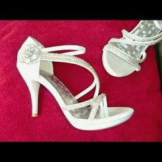 NWOT white high heel sandals + sparkly rhinestones Strappy white patent stiletto high heels with small platform and silver sparkly rhinestones on the straps and a cute flower on the side. Under the flower is velcro so that you can adjust how tight the straps are. Great for wedding! New and never worn. DELICACY Shoes Sandals