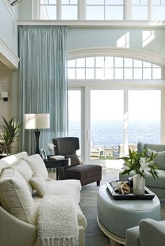 Eclectic Living Room with Sunpan Frances Fabric Winged Chair, Ocean view, Double height living room, Upholstered coffee table