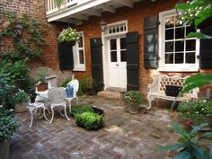 Love red brick, black shutters and white trim...and a courtyard is heavenly!  New Orleans courtyard