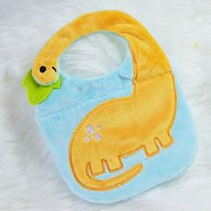 """IN THE HOOP Dino Baby Bib    Made in the 5x7 hoop or larger, this dino baby bob comes in three sizes! 5x7, 6x10, and 8x12! Very easy to make in two to three hoopings. Fabric shown for construction is Shannon Minky Fabric. Comes with a 9 page full color PDF tutorial.    5x7 makes: 6.75"""" wide X 9.45"""" tall"""